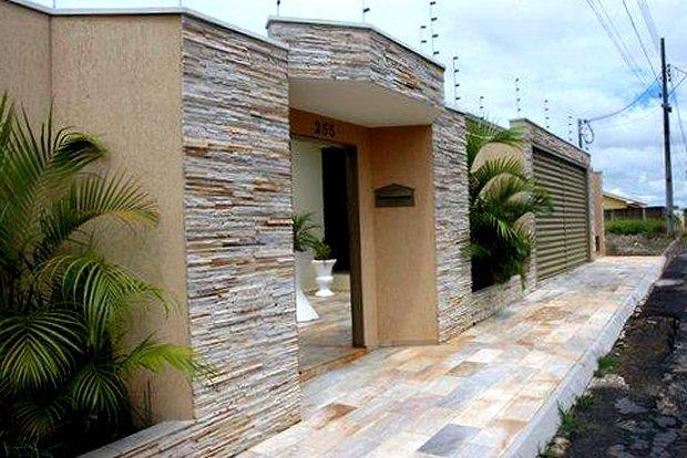 """Muro alto com nichos: entrada principal centralizada, com entrada lateral maior da garagem. Revestimento com pedra """"canjiquinha"""" e plantas que a suavizam."""
