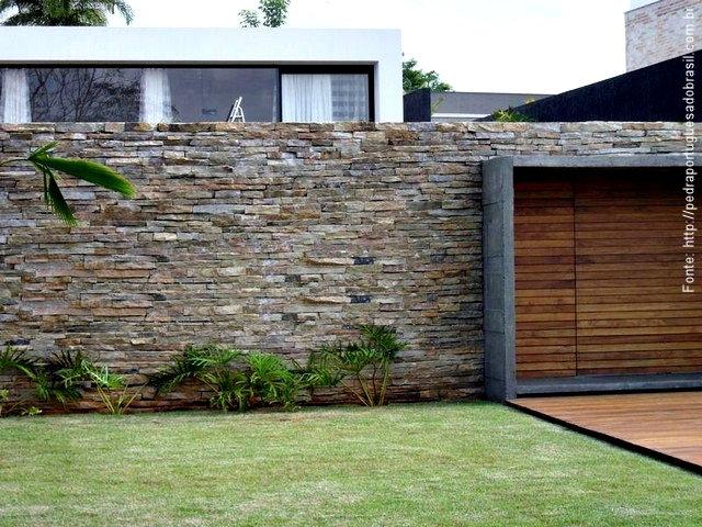 """Alto, um tanto """"pesado"""", mas bem composto, o muro foi revestido com filetes irregulares de pedra ardósia escura em junta seca, o que o deixa sóbrio e sofisticado."""